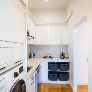Photo of a small contemporary l-shaped utility room in Brisbane with shaker cabinets, quartz benchtops, grey splashback, marble splashback, medium hardwood floors, brown floor, white benchtop, a single-bowl sink, white cabinets, white walls and a stacked washer and dryer.