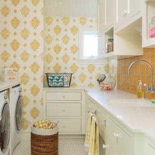 This is an example of a large classic u-shaped separated utility room in Los Angeles with a submerged sink, shaker cabinets, white cabinets, engineered stone countertops, yellow walls, porcelain flooring, a side by side washer and dryer, white floors and white worktops.