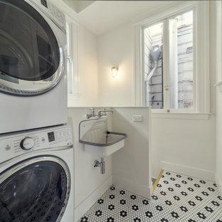Foto di una lavanderia multiuso vittoriana di medie dimensioni con lavatoio, pareti bianche, pavimento con piastrelle in ceramica e lavatrice e asciugatrice a colonna