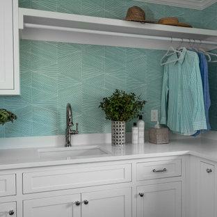 Idéer för att renovera en stor maritim vita u-formad vitt tvättstuga enbart för tvätt, med en undermonterad diskho, skåp i shakerstil, bänkskiva i kvarts, vitt stänkskydd, blå väggar, mörkt trägolv, en tvättmaskin och torktumlare bredvid varandra och brunt golv