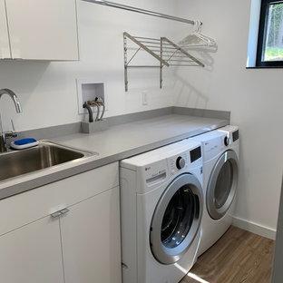 Idee per una sala lavanderia minimalista di medie dimensioni con ante lisce, ante bianche, pareti bianche, pavimento in vinile, lavatrice e asciugatrice affiancate e top grigio