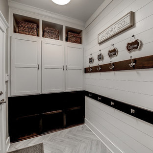 Small traditional single-wall separated utility room in Dallas with a built-in sink, shaker cabinets, grey cabinets, engineered stone countertops, grey walls, laminate floors, a stacked washer and dryer, grey floors and black worktops.