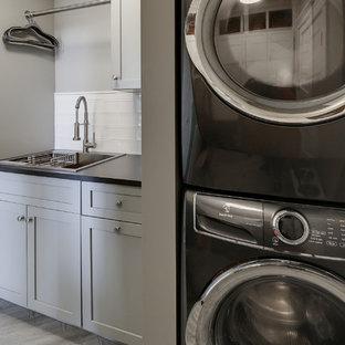 Immagine di una piccola sala lavanderia chic con lavello da incasso, ante in stile shaker, ante grigie, top in quarzo composito, pareti grigie, pavimento in laminato, lavatrice e asciugatrice a colonna, pavimento grigio e top nero