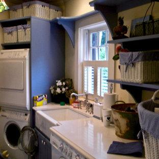 Foto di una lavanderia multiuso classica di medie dimensioni con lavello stile country, ante in stile shaker, ante blu, top in quarzo composito, pareti bianche, pavimento in ardesia, lavatrice e asciugatrice a colonna, pavimento verde e top bianco