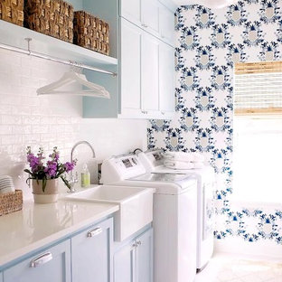 Idée de décoration pour une buanderie champêtre avec un évier de ferme, un placard à porte shaker, des portes de placard bleues, un sol en bois clair, des machines côte à côte, un sol beige, un plan de travail blanc et un mur multicolore.