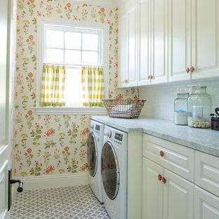 Idéer för mellanstora vintage linjära tvättstugor enbart för tvätt, med luckor med upphöjd panel, vita skåp, marmorbänkskiva, betonggolv, en tvättmaskin och torktumlare bredvid varandra och flerfärgade väggar