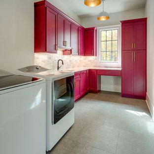 Bild på en vintage vita l-formad vitt tvättstuga, med skåp i shakerstil, röda skåp, vita väggar, en tvättmaskin och torktumlare bredvid varandra och grått golv