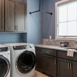 Bild på en stor industriell grå l-formad grått tvättstuga enbart för tvätt, med en undermonterad diskho, skåp i shakerstil, grå skåp, bänkskiva i kvartsit, blått stänkskydd, stänkskydd i keramik, blå väggar, klinkergolv i keramik, en tvättmaskin och torktumlare bredvid varandra och grått golv