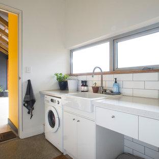 Idées déco pour une buanderie linéaire contemporaine dédiée avec un évier de ferme, un placard à porte plane, des portes de placard blanches, un mur blanc, béton au sol, un sol gris et un plan de travail blanc.