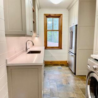 Bild på ett mellanstort vintage vit parallellt vitt grovkök, med en undermonterad diskho, skåp i shakerstil, grå skåp, bänkskiva i kvarts, vita väggar, skiffergolv, en tvättmaskin och torktumlare bredvid varandra, flerfärgat golv och vitt stänkskydd