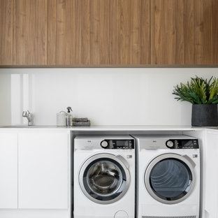 Contemporary l-shaped laundry room in Sydney with flat-panel cabinets, white cabinets, white walls, a side-by-side washer and dryer and white benchtop.