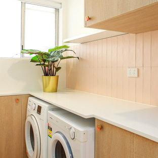 Esempio di una piccola sala lavanderia con ante lisce, ante in legno chiaro, top in quarzo composito, paraspruzzi rosa, paraspruzzi con piastrelle in ceramica, pareti gialle, pavimento in vinile, lavatrice e asciugatrice affiancate, pavimento rosa e top bianco