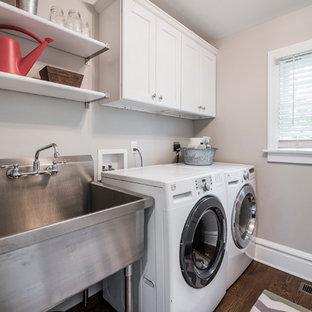 Immagine di una sala lavanderia chic di medie dimensioni con lavatoio, ante in stile shaker, ante bianche, pareti beige, pavimento in legno massello medio e lavatrice e asciugatrice affiancate