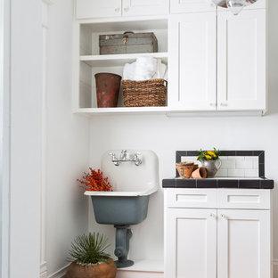 Cette photo montre une buanderie sud-ouest américain avec un évier 1 bac, un placard à porte shaker, des portes de placard blanches, un plan de travail en carrelage, un mur blanc et un sol en carreau de terre cuite.