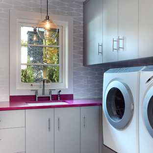 Large contemporary l-shaped utility room in Grand Rapids with a side by side washer and dryer, a submerged sink, flat-panel cabinets, grey cabinets, laminate countertops, grey walls, ceramic flooring, grey floors and pink worktops.