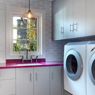 Exempel på ett stort modernt rosa l-format rosa grovkök, med en tvättmaskin och torktumlare bredvid varandra, en undermonterad diskho, släta luckor, grå skåp, laminatbänkskiva, grå väggar, klinkergolv i keramik och grått golv
