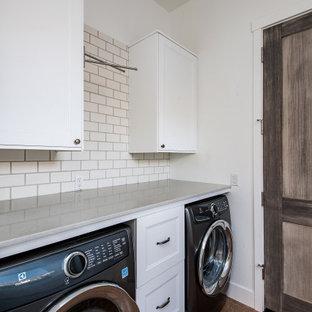 Immagine di una grande lavanderia multiuso con ante in stile shaker, ante bianche, top in superficie solida, paraspruzzi grigio, paraspruzzi in lastra di pietra, pareti bianche, pavimento in cemento, lavatrice e asciugatrice nascoste, pavimento marrone e top grigio