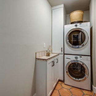 Immagine di un ripostiglio-lavanderia mediterraneo con ante in stile shaker, ante bianche, top piastrellato, pareti verdi, pavimento in terracotta, lavatrice e asciugatrice a colonna e pavimento arancione