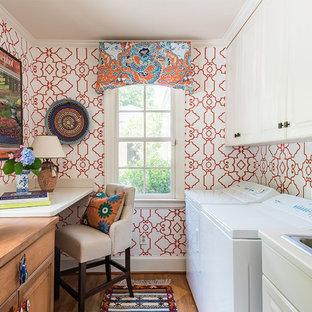 Inredning av en klassisk liten parallell tvättstuga, med bänkskiva i koppar, en tvättmaskin och torktumlare bredvid varandra, luckor med upphöjd panel, en nedsänkt diskho, vita skåp, röda väggar, mellanmörkt trägolv och brunt golv