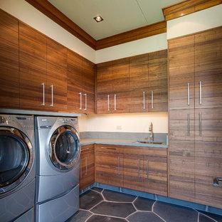 Ispirazione per una lavanderia tropicale con ante lisce, ante in legno scuro, lavatrice e asciugatrice affiancate e pavimento grigio