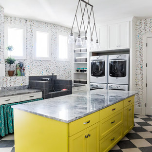 Mid-sized eclectic u-shaped porcelain tile utility room photo in Salt Lake City with an utility sink, shaker cabinets, yellow cabinets, quartzite countertops, multicolored walls and a stacked washer/dryer