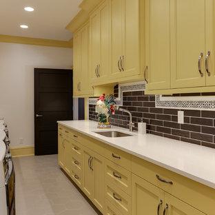 Esempio di una sala lavanderia tradizionale con lavello stile country, ante lisce e ante gialle