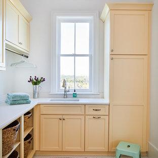 Maritim inredning av en vita l-formad vitt tvättstuga enbart för tvätt, med en undermonterad diskho, bänkskiva i kvarts, vita väggar, vitt golv, skåp i shakerstil och orange skåp