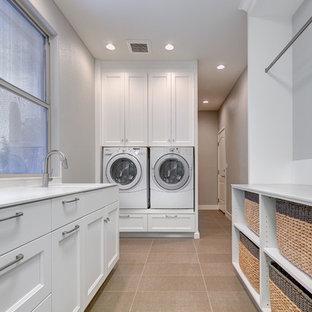 Idéer för mellanstora vintage parallella grovkök, med en rustik diskho, luckor med infälld panel, vita skåp, bänkskiva i kvarts, vitt stänkskydd, stänkskydd i porslinskakel, grå väggar, klinkergolv i porslin och en tvättmaskin och torktumlare bredvid varandra