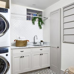 Foto på en vintage grå linjär tvättstuga enbart för tvätt, med en undermonterad diskho, skåp i shakerstil, beige skåp, marmorbänkskiva, vita väggar, klinkergolv i keramik, en tvättpelare och flerfärgat golv