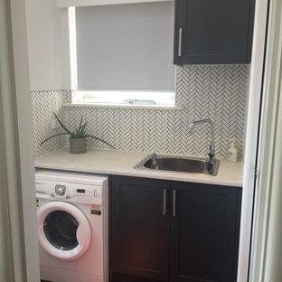 Idee per una piccola lavanderia multiuso contemporanea con lavello a vasca singola, ante in stile shaker, ante grigie, top in laminato, pareti bianche, pavimento in legno massello medio, lavatrice e asciugatrice affiancate, pavimento rosso e top bianco