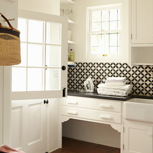 Photo of a traditional laundry room in Los Angeles with a farmhouse sink, terra-cotta floors and red floor.