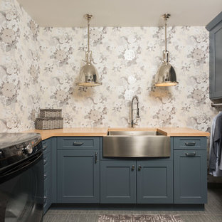 Large transitional u-shaped porcelain tile and gray floor dedicated laundry room photo in Chicago with a farmhouse sink, blue cabinets, wood countertops, a side-by-side washer/dryer, shaker cabinets, multicolored walls and beige countertops