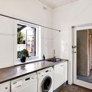 Design ideas for a contemporary single-wall dedicated laundry room in Adelaide with a drop-in sink, flat-panel cabinets, white cabinets, white splashback, subway tile splashback, white walls, a side-by-side washer and dryer, brown floor and brown benchtop.