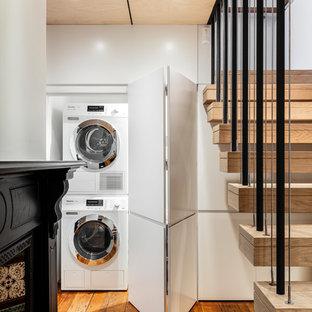 Ispirazione per un ripostiglio-lavanderia design con ante lisce, ante bianche, pareti bianche, pavimento in legno massello medio, lavatrice e asciugatrice a colonna e pavimento marrone