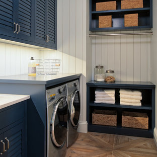 Mid-sized transitional l-shaped light wood floor and beige floor dedicated laundry room photo in Minneapolis with louvered cabinets, blue cabinets, solid surface countertops, white walls and a side-by-side washer/dryer