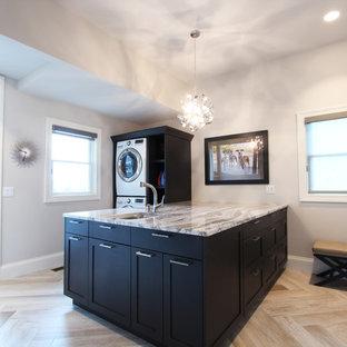 Foto di una grande sala lavanderia chic con lavello sottopiano, ante con riquadro incassato, ante in legno bruno, top in quarzo composito, pareti grigie, pavimento in gres porcellanato, lavatrice e asciugatrice affiancate, pavimento marrone e top beige