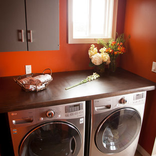 Photo of a transitional laundry room in Los Angeles with brown cabinets, beige floor and brown benchtop.