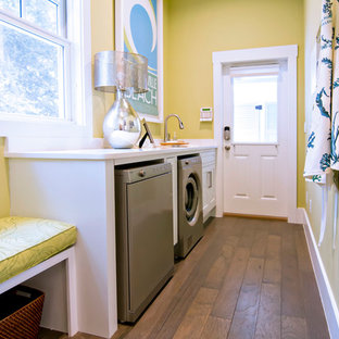 Design ideas for a large world-inspired galley separated utility room in Jacksonville with recessed-panel cabinets, white cabinets, yellow walls, dark hardwood flooring and a side by side washer and dryer.