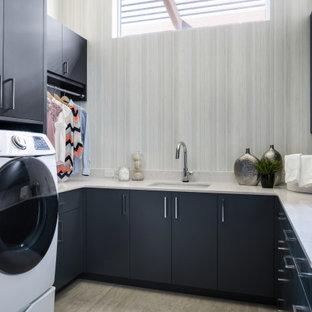 Idéer för att renovera en mycket stor funkis vita u-formad vitt tvättstuga enbart för tvätt, med en undermonterad diskho, släta luckor, blå skåp, bänkskiva i kvarts, vitt stänkskydd, grå väggar, klinkergolv i porslin, en tvättmaskin och torktumlare bredvid varandra och grått golv