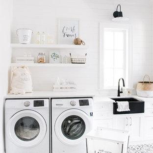 Foto di una grande sala lavanderia country con lavello stile country, ante con riquadro incassato, ante bianche, top in marmo, pareti bianche, pavimento con piastrelle in ceramica, lavatrice e asciugatrice affiancate, pavimento nero e top bianco