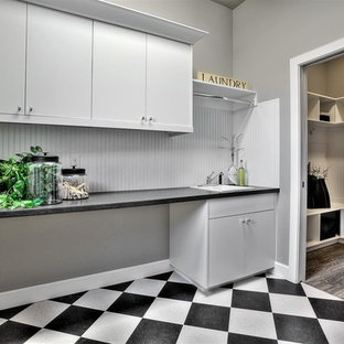 This is an example of a large classic single-wall separated utility room in Boise with a built-in sink, flat-panel cabinets, white cabinets, wood worktops, grey walls, vinyl flooring, a side by side washer and dryer and black worktops.