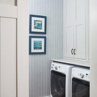 Maritim inredning av en mellanstor vita linjär vitt tvättstuga enbart för tvätt, med skåp i shakerstil, vita skåp, bänkskiva i kvarts, blå väggar, mellanmörkt trägolv, en tvättmaskin och torktumlare bredvid varandra och rött golv