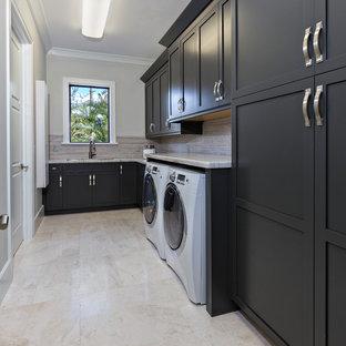 Inspiration för en stor funkis linjär tvättstuga, med en undermonterad diskho, luckor med infälld panel, svarta skåp, marmorbänkskiva, beige väggar, marmorgolv och en tvättmaskin och torktumlare bredvid varandra