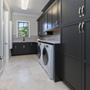 Photo of a large contemporary single-wall utility room in Miami with a submerged sink, recessed-panel cabinets, black cabinets, marble worktops, beige walls, marble flooring and a side by side washer and dryer.
