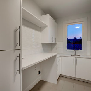 This is an example of a mid-sized contemporary l-shaped dedicated laundry room in Calgary with an undermount sink, flat-panel cabinets, white cabinets, quartz benchtops, white splashback, cement tile splashback, white walls, porcelain floors, a side-by-side washer and dryer, grey floor and white benchtop.