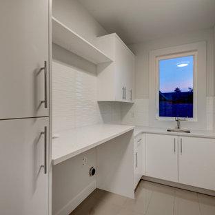 Idéer för en mellanstor modern vita l-formad tvättstuga enbart för tvätt, med en undermonterad diskho, släta luckor, vita skåp, bänkskiva i kvarts, vitt stänkskydd, stänkskydd i cementkakel, vita väggar, klinkergolv i porslin, en tvättmaskin och torktumlare bredvid varandra och grått golv