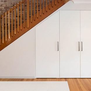 Exempel på en liten modern linjär tvättstuga enbart för tvätt, med vita skåp, vita väggar, mellanmörkt trägolv, tvättmaskin och torktumlare byggt in i ett skåp och brunt golv