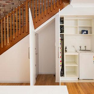 Bild på en liten funkis vita linjär vitt tvättstuga enbart för tvätt, med vita skåp, bänkskiva i koppar, vita väggar, mellanmörkt trägolv, tvättmaskin och torktumlare byggt in i ett skåp och brunt golv