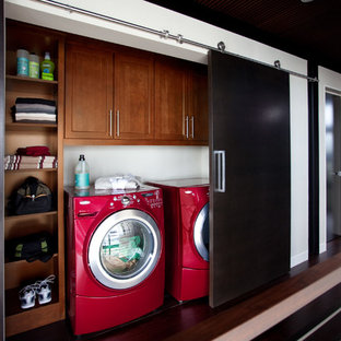 Inspiration for a small contemporary single-wall dark wood floor laundry closet remodel in Other with recessed-panel cabinets, medium tone wood cabinets, white walls and a side-by-side washer/dryer