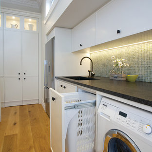 Utility room - contemporary galley light wood floor and brown floor utility room idea in Auckland with white cabinets, laminate countertops, white walls and a side-by-side washer/dryer
